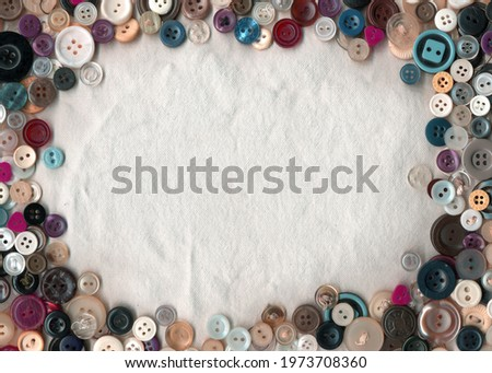 Sewing color buttons frame on fabric texture background. Collection of assorted spare clothes buttons vintage. Sewing tools close up.  Royalty-Free Stock Photo #1973708360