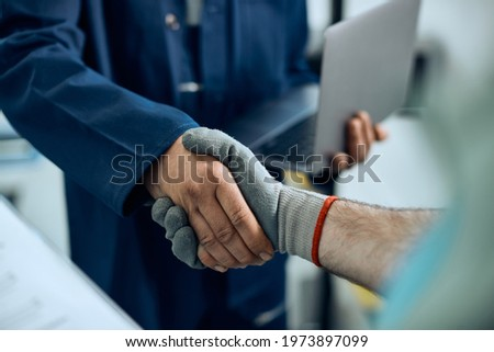 Close-up of auto repairman greeting workshop manager and handshaking with him at repair shop.  Royalty-Free Stock Photo #1973897099