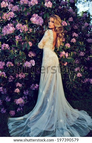 beautiful blonde bride in a luxurious wedding dress in garden with blossom #197390579