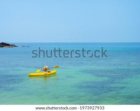 Asian tourist on yellow Kayak boat in tropical island blue sea under bright sun in summer. Koh Kood - Thailand