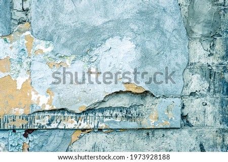 Damaged blue wall texture background. Creative backdrop. Old, closed factory building wall fragment. Weathered and cracked bricks with concrete and peeled off blue paint. Close up, copy space Royalty-Free Stock Photo #1973928188