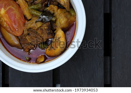 Selective focus and close up picture of beef dalca served during Eid Mubarak. Dalca is a stewed vegetable curry with lentils add meat that is famously served with briyani and tomato rice.