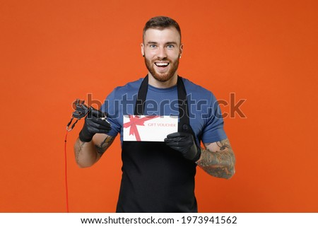 Excited professional tattooer master artist tattooed man in apron hold gift certificate machine black ink in jar equipment for making tattoo art on body isolated on brown background studio portrait