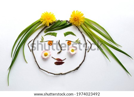 Flower beauty. An image of a child's face made of branches and leaves, flowers, blades of grass. White isolated background. Girl cartoon character.
