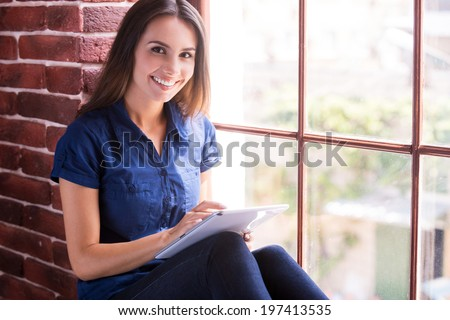Examining her brand new gadget. Cheerful young woman working on digital tablet and smiling while sitting on the window sill #197413535