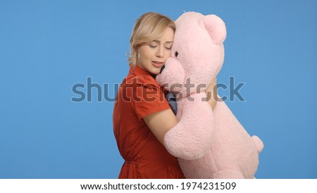 Young woman talking, hugging and kissing with a big teddy bear. Indoor studio shot isolated on blue background.