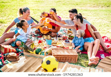 Multiracial families having fun together with kids at pic nic barbecue party - Joy and love life style concept with mixed race people toasting juices with children at park - Warm bright filter