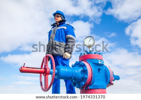 Oil, gas industry. The mechanic - the repairman, gas production operator opens the valve, gas equipment and fitting at the well Royalty-Free Stock Photo #1974331370