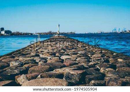 clear blue sky on the pier large stones in the foreground . High quality photo