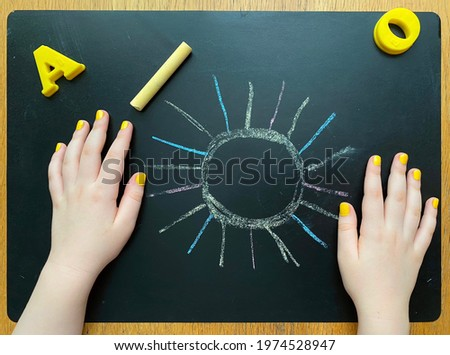 Children's creativity, drawing on the blackboard with crayons, colorful drawings, yellow manicure, hands, art education, picture sun, alphabet letters