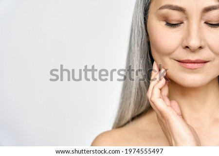 Senior older middle aged Asian woman with grey hair and radiant face with perfect skin. Advertising of rejuvenating skincare and makeup for natural radiant glow and healthy skin. Copy space. Royalty-Free Stock Photo #1974555497