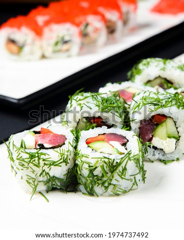 Sushi rolls with tuna, cucumber and cream-cheese in chopped dill. Served on a white plate over black background. Traditional Japanese cuisine concept, sushi recipe.