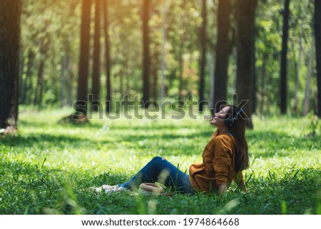 A beautiful young asian woman enjoy listening to music with headphone with feeling happy and relaxed in the park Royalty-Free Stock Photo #1974864668
