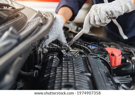 Automobile mechanic repairman hands repairing a car engine automotive workshop with a wrench, car service and maintenance,Repair service. Royalty-Free Stock Photo #1974907358