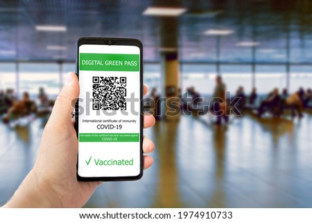 The digital green pass with the QR code on the screen of a mobile ina man hand with blurred airport in the background. Concept of immunity from Covid-19