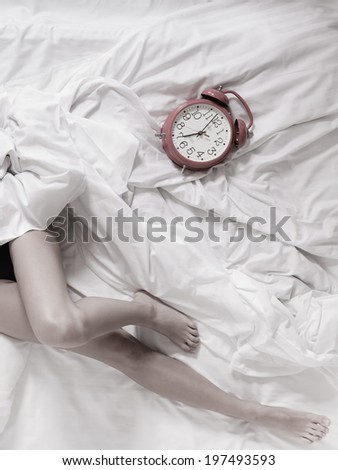 Closeup of sexy female legs with alarm clock on the bed. Woman lazy girl relaxing lazing in bedroom. #197493593