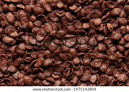 Breakfast chocolate cereals background, flat lay. Full-frame of cocoa cornflakes, macro image. Top view with a multitude of chocolate flakes. Royalty-Free Stock Photo #1975142804