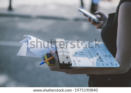 Assistant director with clapperboard on set. Close-up of firecrackers for filming a movie, advertising, TV series. Modern photography technique. Royalty-Free Stock Photo #1975190840