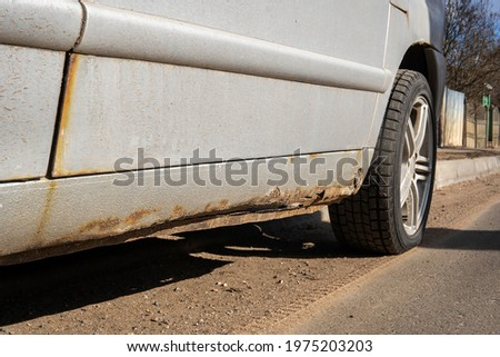 Sheet metal corrosion over wheel of old white car. Rusty messy surface. Damaged grunge dirty texture from road salt. Rust background. Protecting the automobile concept. Resistance test. Paint work. Royalty-Free Stock Photo #1975203203