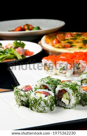 Sushi rolls with tuna, cucumber and cream-cheese in chopped dill. Served on a white plate over white background. Traditional Japanese cuisine concept, sushi recipe. Pizza and salad on the background.