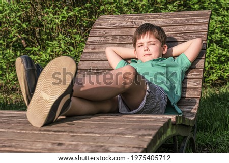 Boy of 8 years in T-shirt and shorts lies on wooden deck chair in the sun against background of green leaves. The boy in relaxed, lazy position, narrowed his eyes. Royalty-Free Stock Photo #1975405712