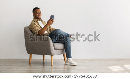 Cheerful African American Guy Using Mobile Phone With New Application Sitting In Armchair Over Gray Wall Background. Gadgets And Mobile Communication Concept. Panorama, Empty Space For Text Royalty-Free Stock Photo #1975431659