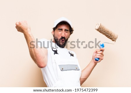 young painter bearded man celebrating his success and holding a