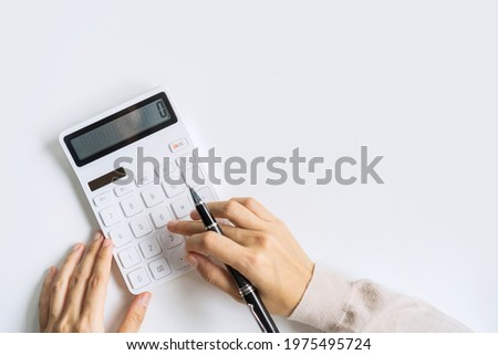 Accountant using calculator on desk office on white background with copy space, Top view Royalty-Free Stock Photo #1975495724