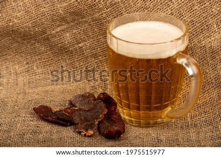 Pieces of dried caviar and a mug of beer on a table covered with a homespun cloth with a rough texture. Close-up, selective focus.