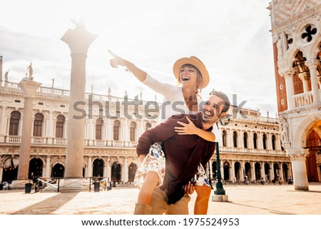 Couple of tourists on vacation in Venice, Italy - Two lovers having fun on city street at sunset - Tourism and love concept Royalty-Free Stock Photo #1975524953