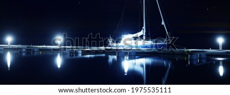 Blue sloop rigged yacht moored to a pier in marina at night. Clear twilight sky, stars, starlight, moonlight, lots of lights. Concept landscape. Copy space, graphic resources. Stockholm archipelago