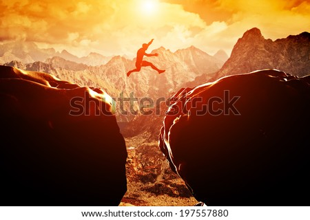 Man jumping over precipice between two rocky mountains at sunset. Freedom, risk, challenge, success. Royalty-Free Stock Photo #197557880