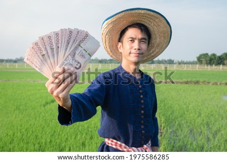 Thai Money banknote holded by Asian farmer man wears blue shirt at green rice farm. Focus at banknote and blur man. Selective focus image.  Royalty-Free Stock Photo #1975586285