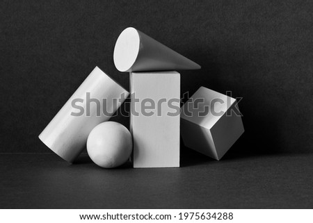 Platonic solids figures geometry. Abstract geometrical objects still life composition. Three-dimensional rectangular prism, cylinder pyramid cube, sphere on black gray background. Royalty-Free Stock Photo #1975634288