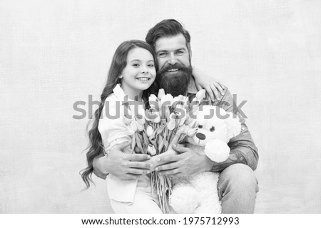 Fabulous gift for little one. Happy family celebrate holiday. Little child and bearded man hold flowers and toy. Small daughter hug father. Gift store. Toyshop. Floral shop. Birthday gift Royalty-Free Stock Photo #1975712993