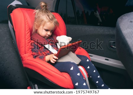 Cute caucasian little child sitting at safety car seat for children, fastened by safety belts, watching cartoons and videos at digital device, evening time, holding bear toy, funny facial expression. Royalty-Free Stock Photo #1975749767