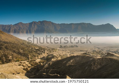 Hindu temple Pura Luhur Poten standing on Segara Wedi volcanic ashes valley, bathed in morning mist and overlooked by arid mountains Royalty-Free Stock Photo #1975750121