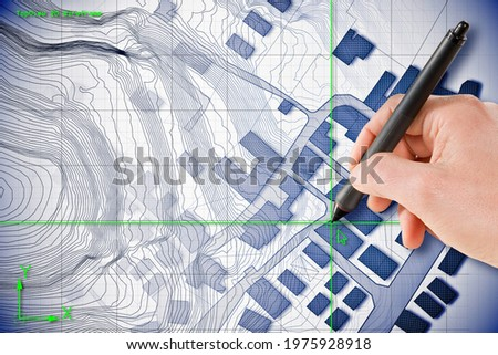 Architect drawing with a digital pen over an imaginary cadastral map of territory with buildings and roads drawn with a CAD (Computer-Aided-Design) computer software in dwg format file.