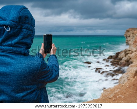 A woman take a photo of the sea on smartphone, female travels along the coast in the cold season