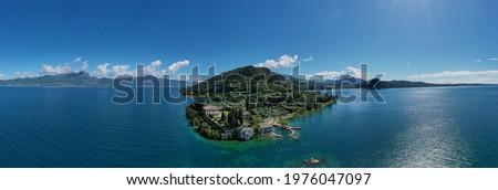 Panorama of punta san vigilio.  Aerial view of Parco Baia delle Sirene, Lake Garda, Italy. Top view of baia delle sirene on the coastline of Lake Garda. Baia delle Sirene on the coastline. Royalty-Free Stock Photo #1976047097