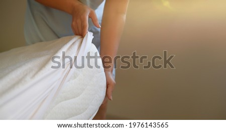 Woman puts a cover on the mattress to protect it from water and house dust mites Royalty-Free Stock Photo #1976143565
