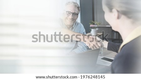 Composition of smiling businessman and businesswoman shaking hands in office with motion blur. global business, partnership and success concept digitally generated image.