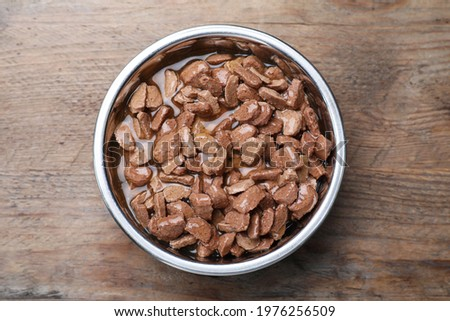 Wet pet food in feeding bowl on wooden table, top view Royalty-Free Stock Photo #1976256509