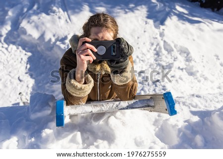 Portrait from above of a young man in winter coat perched on a ladder in the snow, taking a picture to the photographer with his mobile phone.