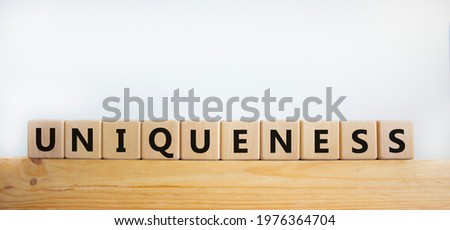 Inclusiveness and uniqueness symbol. Wooden cubes with the word 'uniqueness' on wooden block. Beautiful white background. Business, inclusiveness and uniqueness concept. Copy space.