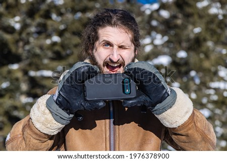 Dramatically ironic portrait of a young man in a winter coat taking a picture with his mobile phone while making an exaggerated funny face.