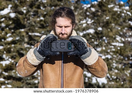 Funny and ironic portrait of a young man in a winter coat taking a picture with his mobile phone while making a funny, concentrated face.
