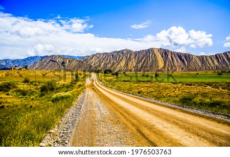 The road through the mountain valley. Mountain valley road landscape. Road in mountain valley. Valley road in mountains