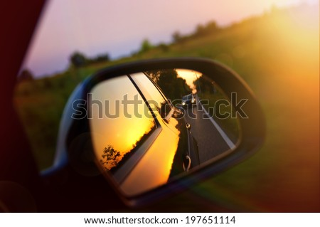 Driving at sunset - peek into a rear view mirror Royalty-Free Stock Photo #197651114