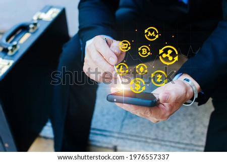businessman using mobile phone check cryptocurrency exchange with graphic graph chart and crypto currency icon, internet security technology, stock market, cryptocurrency and business strategy concept